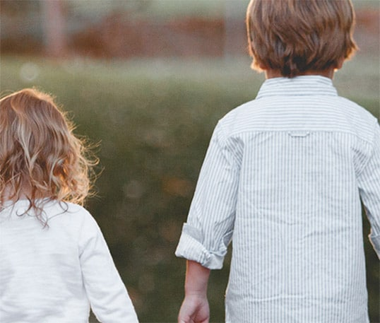 Two small children (a boy and a girl) holding hands, walking in a field, with their backs facing the camera.